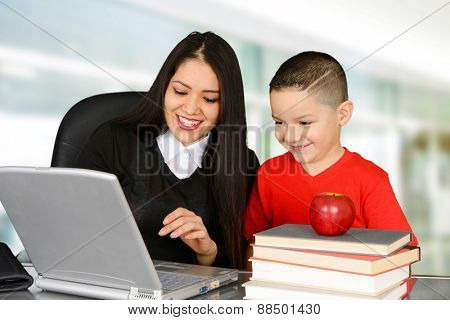 Schoolboy and teacher looking at laptop in class