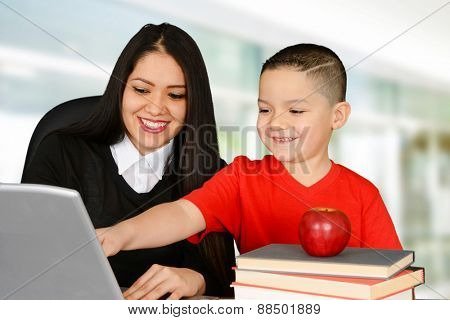 Young teacher and her pupil looking at laptop