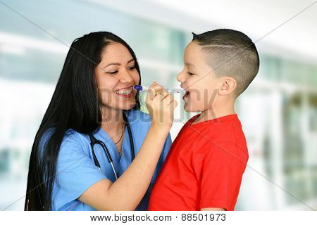 Young female nurse checking up little boy in red t-shirt