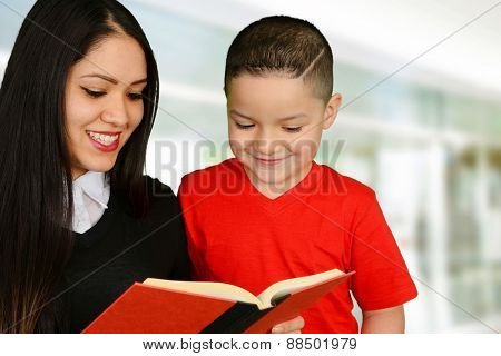 Happy mother reading a book to her smiling son