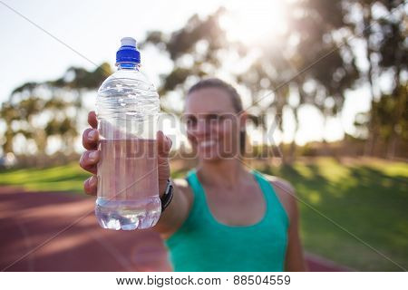 Female athlete holding up a water bottle to the camera with lovely back light