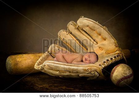 Sleeping newborn baby sleeping in an old baseball glove