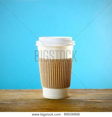 Paper cup on wooden table on blue background