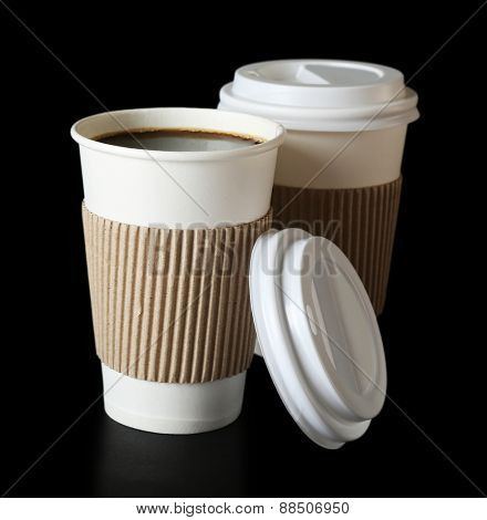 Paper cups of coffee on black background