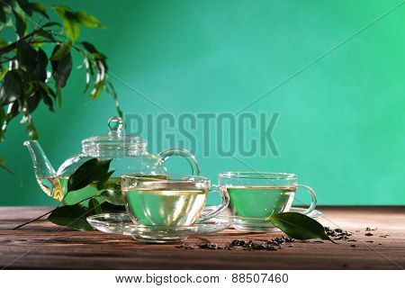 Cups of green tea on table on green background