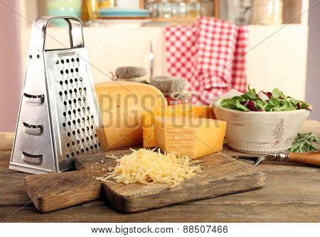 Grated cheese on wooden table on cutting board in kitchen