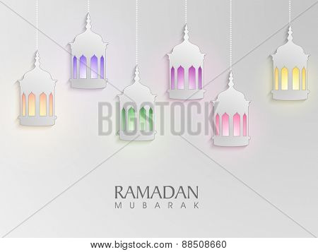 Hanging illuminated arabic lamps or lanterns on grey background for islamic holy month of prayer, Ramadan Kareem celebration.