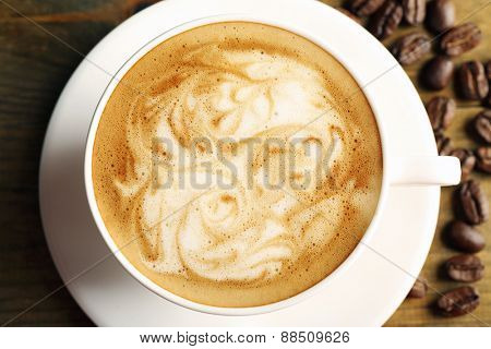 Cup of coffee latte art with grains on wooden table, top view