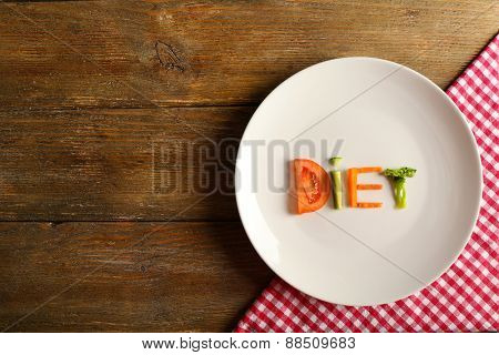 Word DIET made of sliced vegetables in white plate with napkin on wooden background