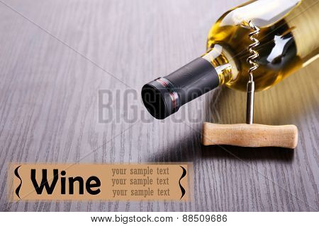 Bottle of wine with corkscrew on wooden table background