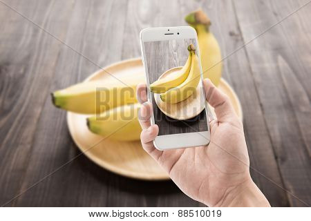 Taking Photo Of Bananas On Wooden Background.