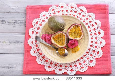 Passion fruit on plate on color wooden background