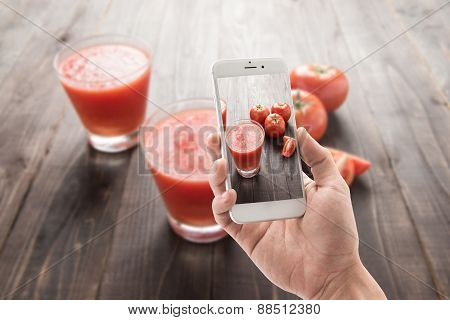 Taking Photo Of Vegetable Smoothie Made Of Red Ripe Tomatoes On Wooden Table.