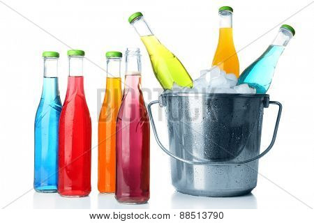 Bottles of tasty drink and metal bucket with ice isolated on white