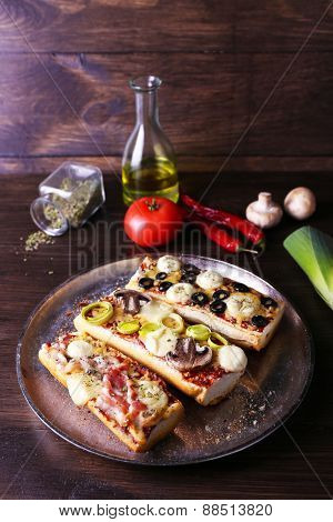 Different sandwiches with vegetables and cheese on metal tray on table close up