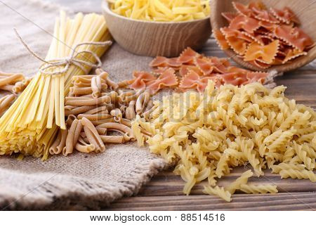 Different types of pasta on sackcloth background