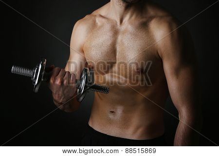 Muscle young man holding dumbbell on dark background