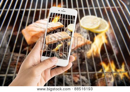 Taking Photo Of Grilled Salmon With Lemon On The Flaming Grill.