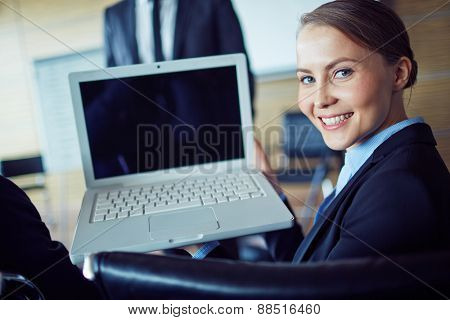 Happy businesswoman looking at camera during presentation