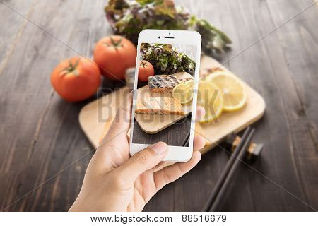 Taking Photo Of Grilled Salmon On Cutting Board On Wooden Background.