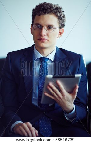 Elegant young businessman holding touchpad