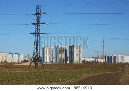 Power Line And Houses Against  Blue Sky