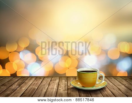 Tea cup on the wood in the bokeh city light