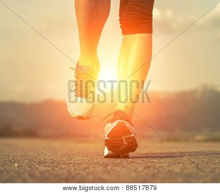 Runner athlete feet running on road under sunlight.