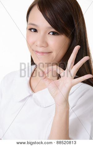 Asian nurse with give you an Okay sign on white background.