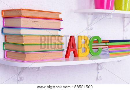 Shelves with stationery in child room close-up