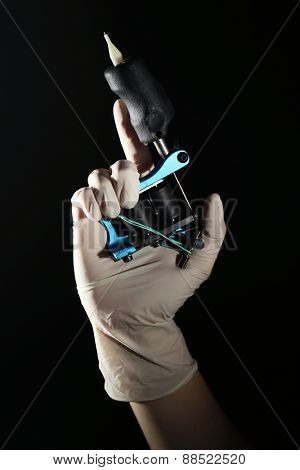 Tattoo artist holding tattoo machine, on dark background