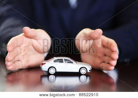Man and model of car on wooden table, closeup