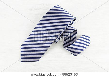 Striped tie on wooden table background