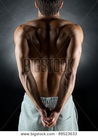 sport, bodybuilding, strength and people concept - young man standing over black background from back and flexing muscles