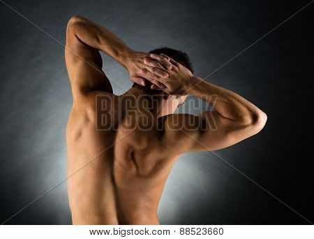 sport, bodybuilding, strength and people concept - young man standing over black background from back