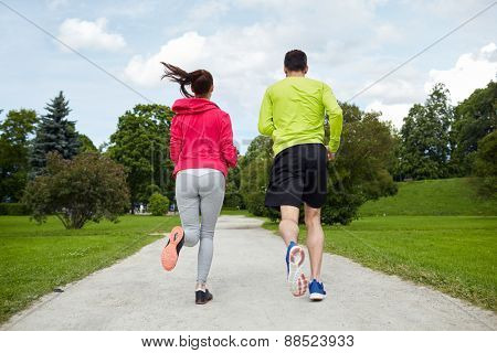 fitness, sport, friendship, people and lifestyle concept - smiling couple running outdoors from back