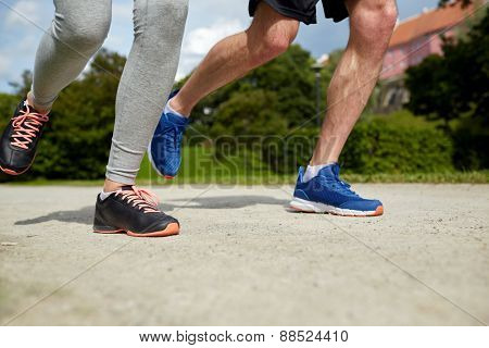 fitness, sport, friendship, people and lifestyle concept - close up of couple running outdoors