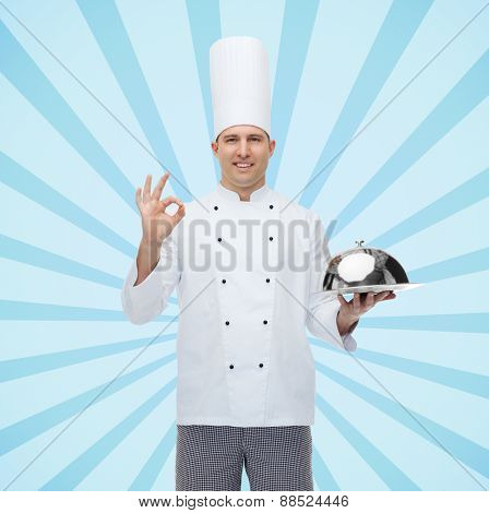 cooking, profession, gesture and people concept - happy male chef cook holding cloche and showing ok sign over blue burst rays background