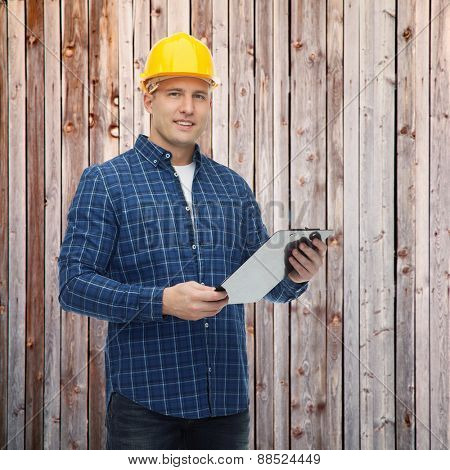 repair, construction, building, people and maintenance concept - smiling male builder or manual worker in helmet with clipboard over wooden fence background
