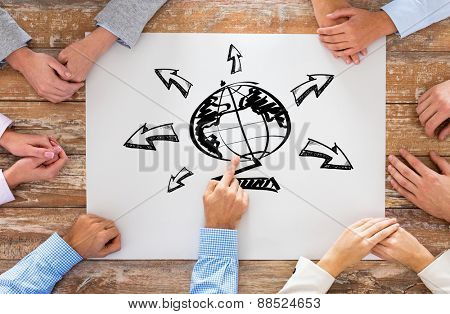 global business, people and team work concept - close up of creative team sitting at table and pointing finger to globe picture on paper in office