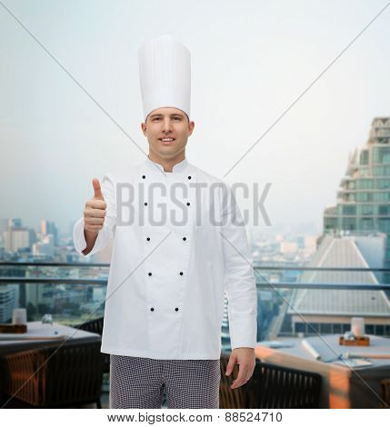 cooking, profession, gesture and people concept - happy male chef cook showing thumbs up over city restaurant lounge background