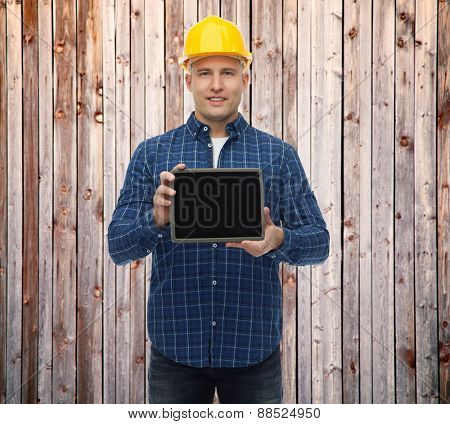 repair, construction, building, people and maintenance concept - smiling male builder or manual worker in helmet showing tablet pc computer blank screen over wooden fence background