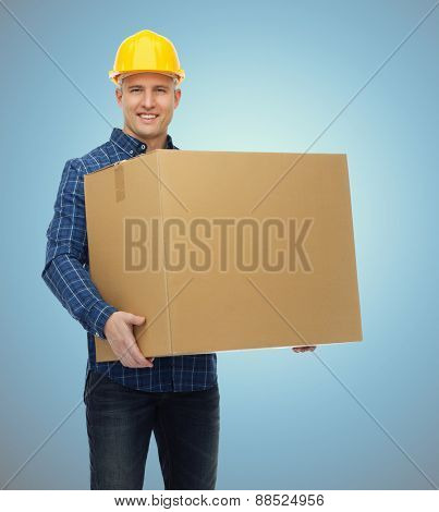 repair, construction, building, people and maintenance concept - smiling male builder or manual worker in helmet carrying big cardboard box over blue background