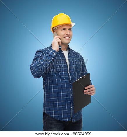 construction, building, people, technology and maintenance concept - smiling male builder or manual worker in helmet with clipboard calling on smartphone over blue background