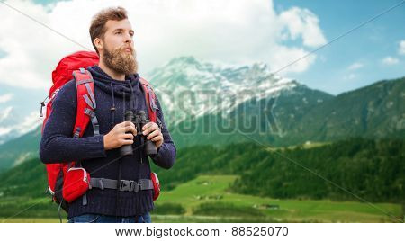 adventure, travel, tourism, hike and people concept - man with red backpack and binocular over alpine mountains background
