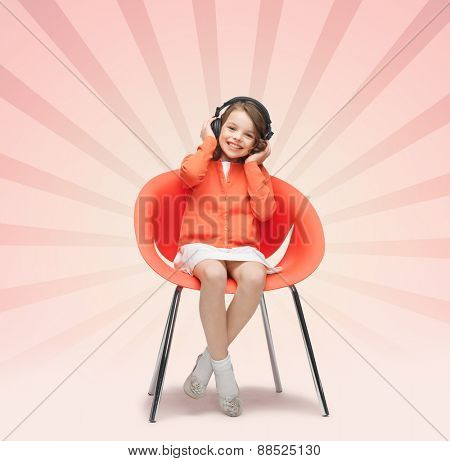 people, leisure, hobby and entertainment concept - happy little girl listening to music in headphones over pink burst rays background