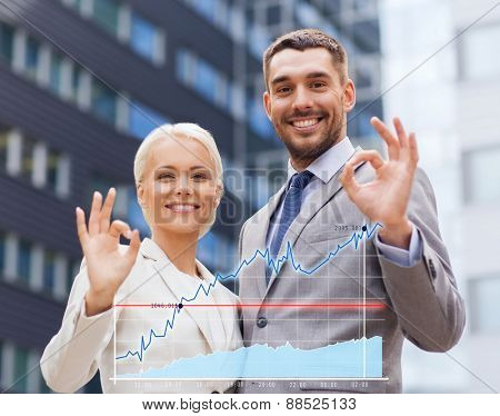 business, partnership, gesture success and people concept - smiling businessman and businesswoman making ok gesture over office building background