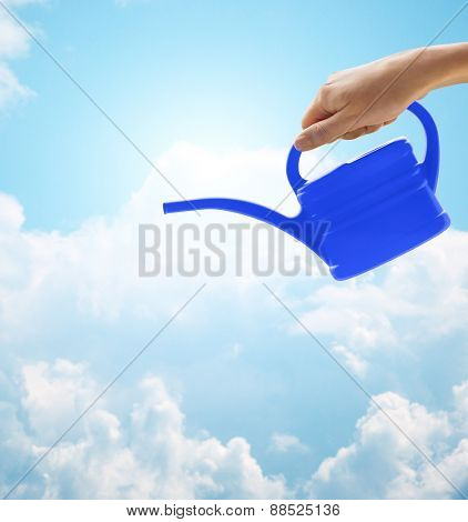 people, gardening and profession concept - close up of woman or gardener hand holding watering can over blue sky with clouds