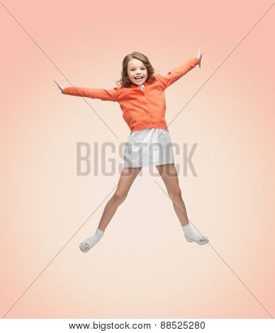 people, childhood, happiness, motion and freedom concept - happy girl in casual clothes jumping high over beige background