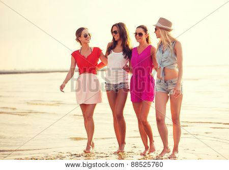 summer vacation, holidays, travel and people concept - group of smiling young women in sunglasses and casual clothes on beach